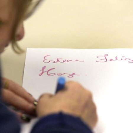 """foto mostra uma pessoa escrevendo """"Estou Feliz Hoje"""" em um papel branco"""