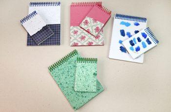 Foto mostra quatro kits. Cada kit contém um bloco de anotação grande e outro mini