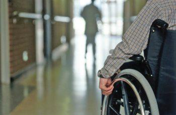 Cadeirante observa pessoa caminhando à sua frente em corredor largo