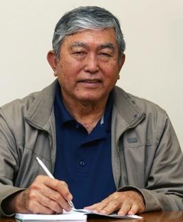 Foto de Thoshio Katsurayama, um senhor com cabelos curtos e grisalhos, com uma camisa polo azul e uma jaqueta cinza