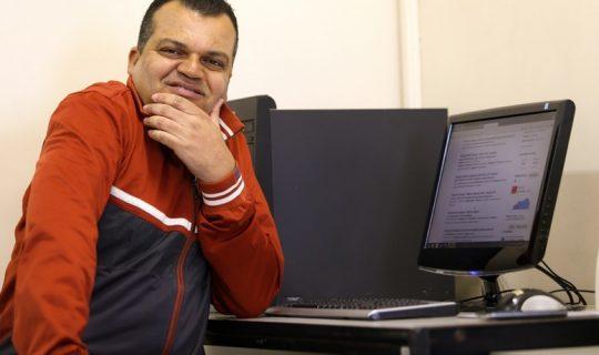 Foto de um homem de meia idade em frente à um computador. Ele olha na direção da câmera e está com a mão esquerda apoiada no queixo
