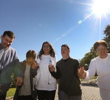Foto em plano aberto de um espaço aberto, com 5 pessoas caminhando sob o sol e sorrindo