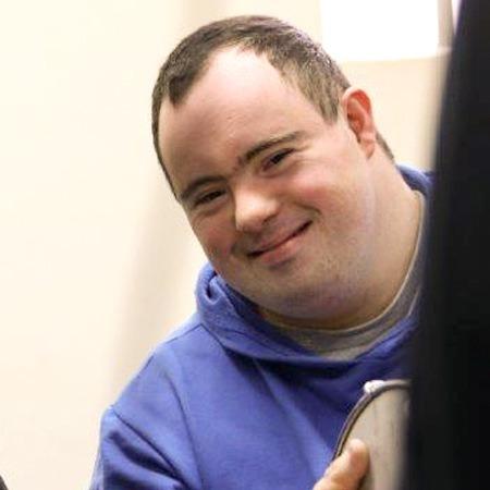 Foto de um jovem com Síndrome de Down sorrindo na direção da câmera