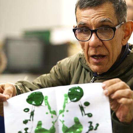 Foto de um senhor grisalho, com óculos, segurando uma folha com pintura abstrata em tinta verde