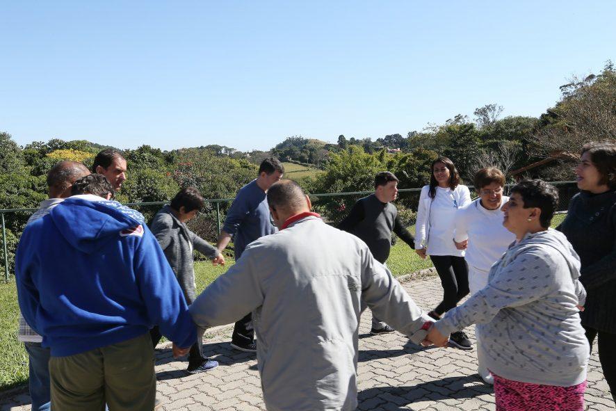 Foto de uma roda de pessoas de mãos dadas em um espaço aberto e arborizado