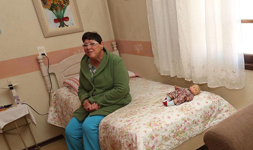 Foto de uma senhora sentada em uma cama, com uma boneca ao lado. O quarto tem as paredes rosas e é iluminado