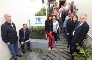 Foto da entrada da Apabex, com diversas pessoas reunidas e sorrindo na direção da câmera