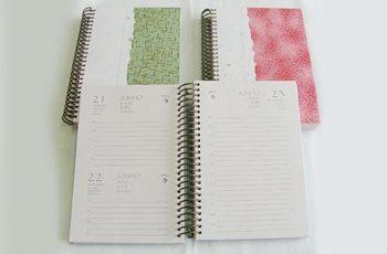 Foto com três agendas, duas fechadas com capas artesanais e uma aberta