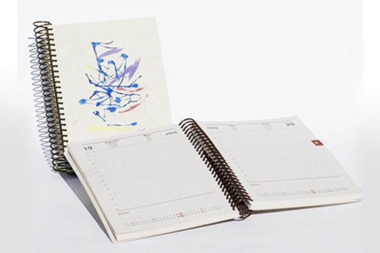 Foto mostra duas agendas de compromissos. Uma está fechada mostrando a capa e a outra mostra as páginas de anotação