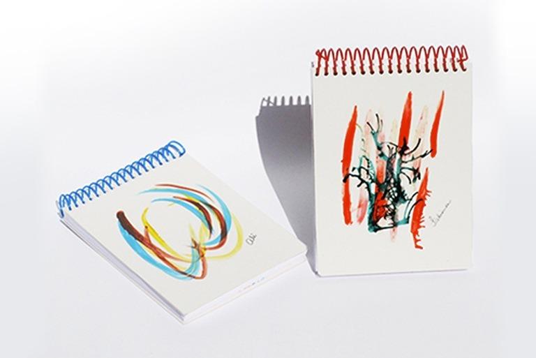 Foto de dois blocos de anotação com ilustrações artísticas