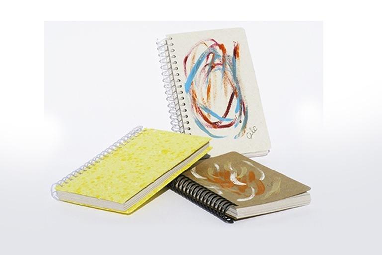 Foto com três cadernetas com capas artesanais