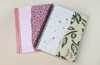 Foto com dois cadernos com capas artesanais feitas com colagens e papel reciclado