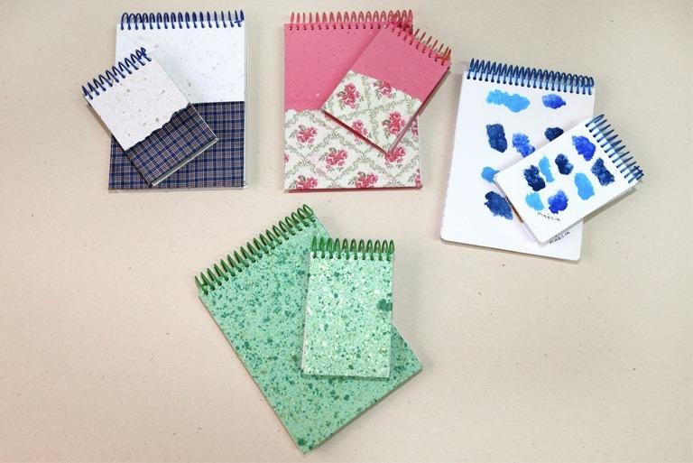 Foto com 4 kits com 2 blocos de anotação com capaz artesanais