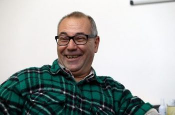 Foto de um homem com cabelos curtos e grisalhos, sorrindo. Ele usa óculos e uma camisa de flanela xadrez verde