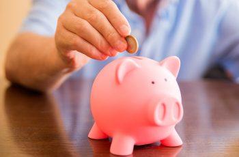 Foto de uma mão depositando uma moeda em um cofre de porquinho