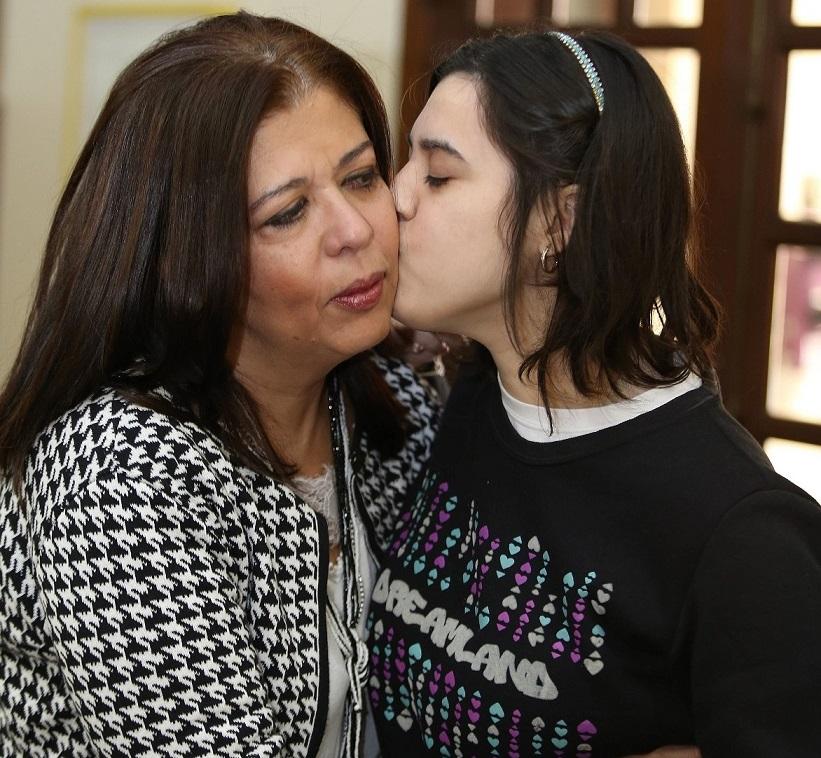 Foto de uma mulher recebendo um beijo na bochecha de uma moça