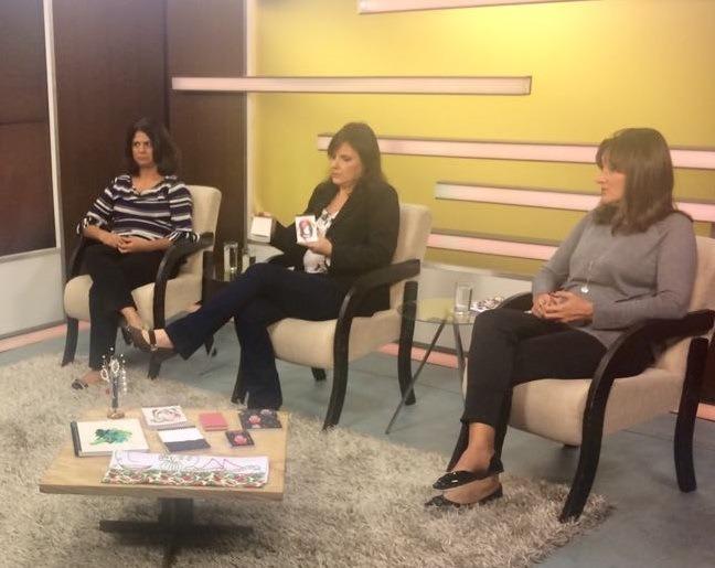 Foto de três mulheres sentadas lado a lado em um estúdio