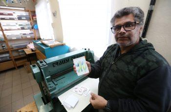 Homem com cabelos grisalhos e óculos exibe um cartão em frente ao furador para encadernação