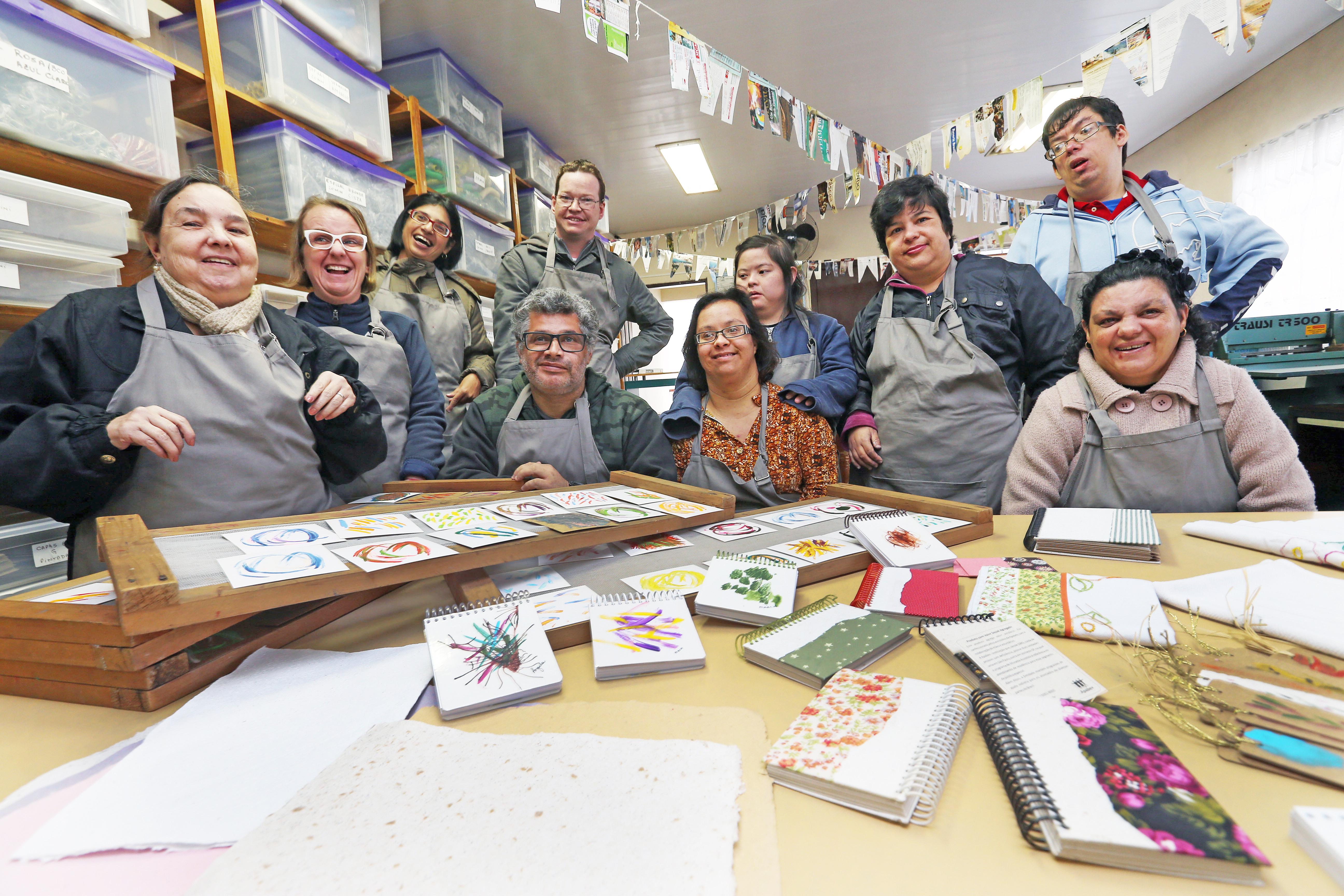 Foto em plano aberto de um grupo com diversas pessoas usando aventais e com encadernações e pinturas espalhadas em uma mesa. Elas sorriem na direção da câmera