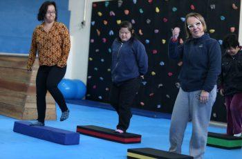 Foto de três mulheres de diferentes idades em frente a pequenos degraus durante uma dinâmica em grupo