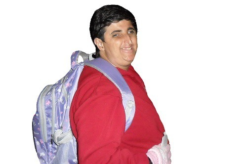 Uma mulher com cabelos curtos e escuros sorri. Ela usa um moletom vermelho e tem uma mochila lilás nas costas